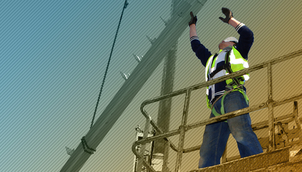 Construction worker on scaffold directing a crane load